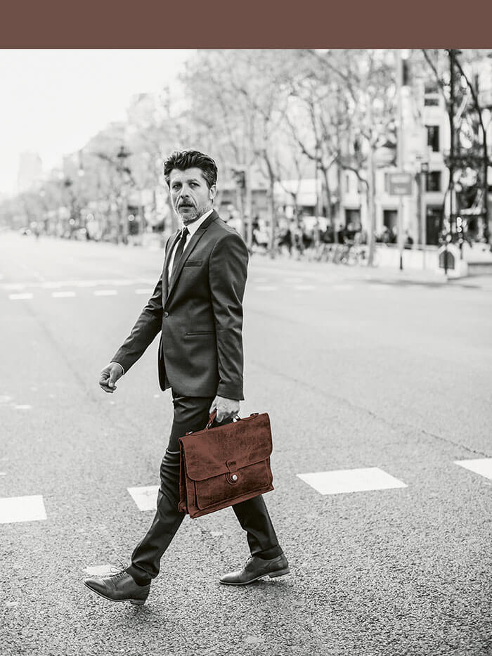 Businessman with leather bag crosses a street