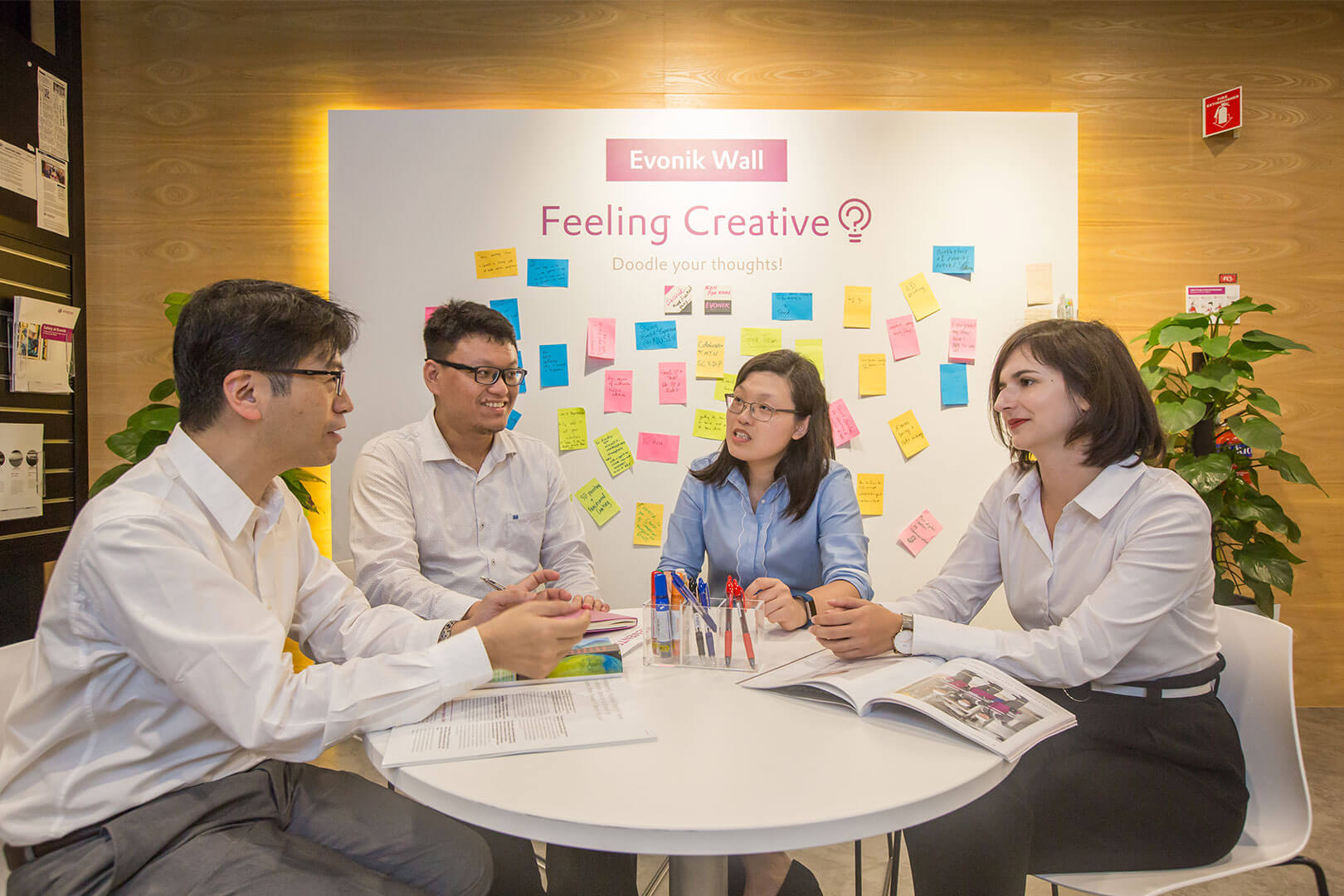 Employees of Evonik sit at the table